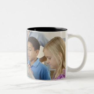 students and teacher with globe Two-Tone coffee mug