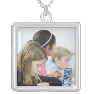 Students doing math work in classroom silver plated necklace