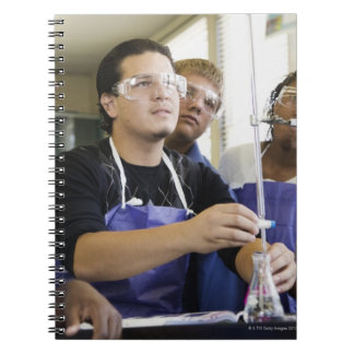 Students performing experiment in chemistry lab notebook