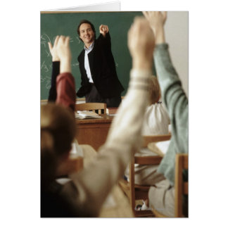 Students raising their hands in classroom greeting card