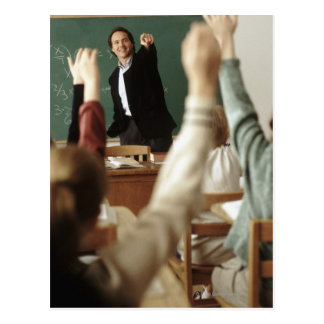 Students raising their hands in classroom postcard