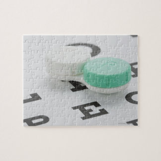 Studio shot of contact lens case on eye chart jigsaw puzzle