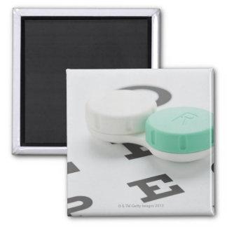 Studio shot of contact lens case on eye chart magnet