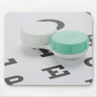 Studio shot of contact lens case on eye chart mouse mat