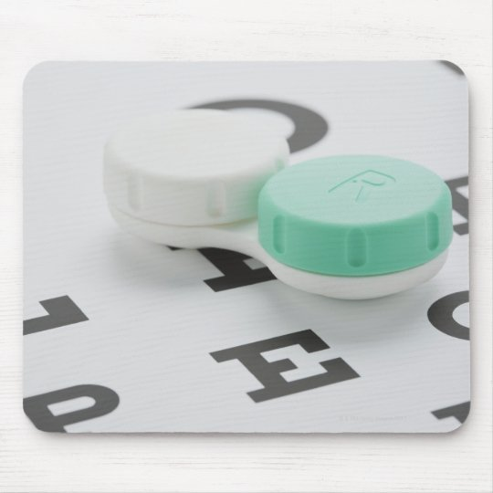 Studio shot of contact lens case on eye chart mouse mat