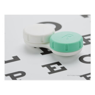 Studio shot of contact lens case on eye chart postcard