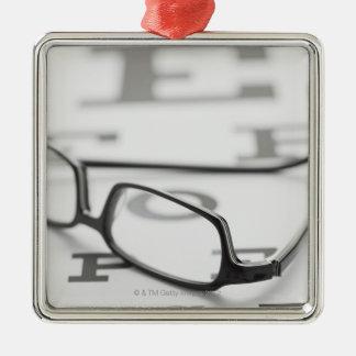 Studio shot of eyeglasses on eye chart ornament