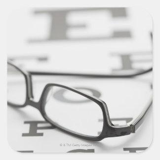 Studio shot of eyeglasses on eye chart square sticker