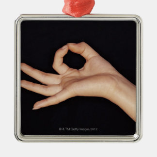 Studio shot of hand gesturing a sign Silver-Colored square decoration