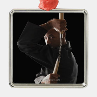 Studio shot of man exercising with nunchaku christmas ornament