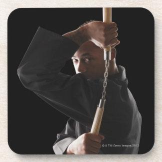 Studio shot of man exercising with nunchaku coaster
