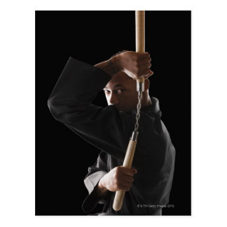 Studio shot of man exercising with nunchaku postcard