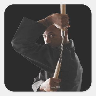 Studio shot of man exercising with nunchaku square sticker