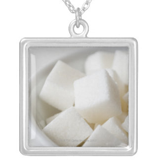 Studio shot of sugar cubes in bowl silver plated necklace