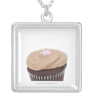 Studio still life shot of cupcakes. silver plated necklace