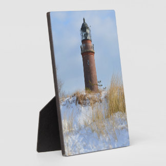 Sturdy Lighthouse on a Rocky Coast in Winter Display Plaque