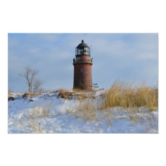 Sturdy Lighthouse on a Rocky Coast in Winter Poster