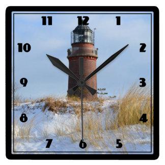 Sturdy Lighthouse on a Rocky Coast in Winter Wallclocks