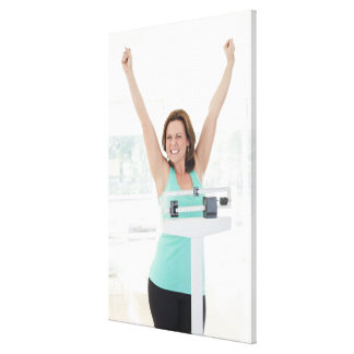 Successful weight loss. Happy woman weighing Canvas Print