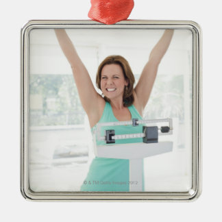 Successful weight loss. Happy woman weighing Christmas Ornament