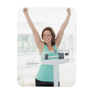 Successful weight loss. Happy woman weighing Flexible Magnet