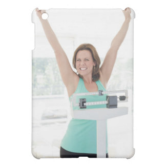 Successful weight loss. Happy woman weighing iPad Mini Case