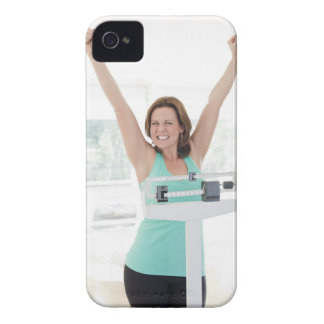 Successful weight loss. Happy woman weighing iPhone 4 Cover