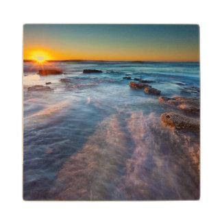 Sun rays illuminate the Pacific Ocean Maple Wood Coaster