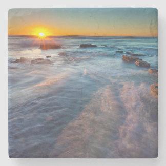 Sun rays illuminate the Pacific Ocean Stone Coaster