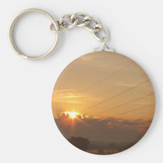 Sun surfaces above the clouds over foggy Pasture Basic Round Button Key Ring