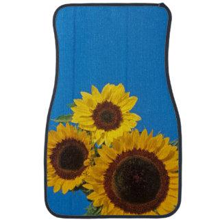 Sunflowers against blue fence car mat