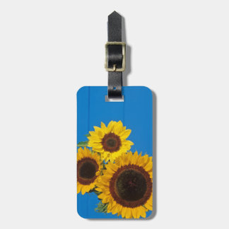 Sunflowers against blue fence luggage tag