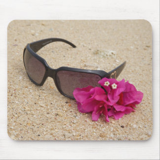 Sunglasses and bougainvillia flowers on coral mouse pad