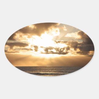 SUNRISE OVER THE SEA OVAL STICKER