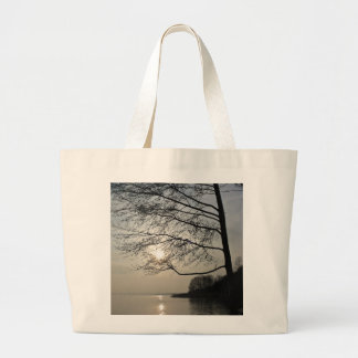 Sunset in the winter tree at the lake large tote bag