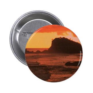 Sunset on a rocky coast button