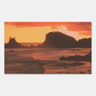 Sunset on a rocky coast rectangular sticker