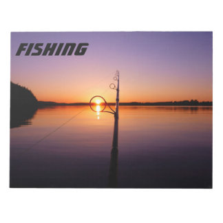 Sunset on a summer lake seen through a fishing rod notepad