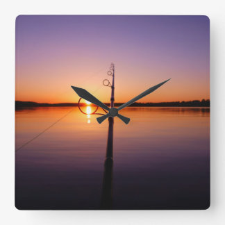 Sunset on a summer lake seen through a fishing rod square wall clock
