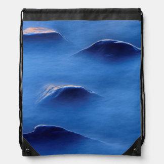 Sunset on rocks protruding through foamy water drawstring bag