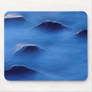 Sunset on rocks protruding through foamy water mouse mat