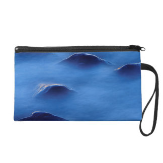 Sunset on rocks protruding through foamy water wristlet clutch