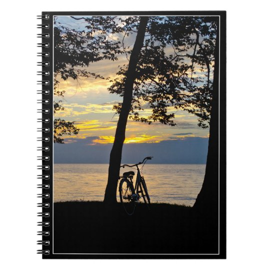Sunset over lake with bicycle notebook