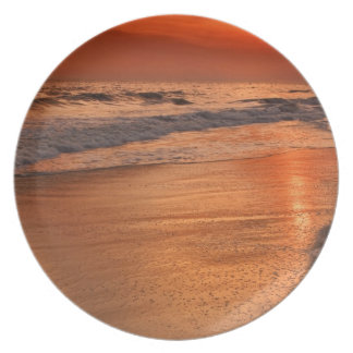 Sunset reflections off clouds and ocean shore plate