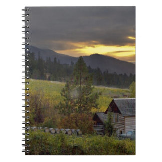 Sunset sky over vineyards and historic log cabin notebook
