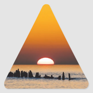 Sunset with angler on shore of the Baltic Sea Triangle Sticker