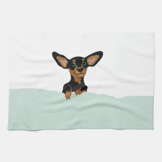 Supercute dachshund puppy under green duvet tea towel