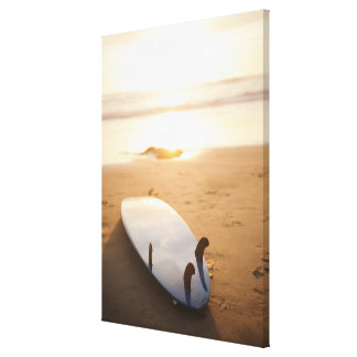 Surfboard laying on beach at sunset canvas print