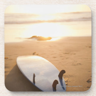 Surfboard laying on beach at sunset coaster