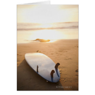 Surfboard laying on beach at sunset greeting card